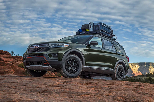 Side profile of a 2021 Ford Explorer pictured taking a sharp turn on a rugged landscape
