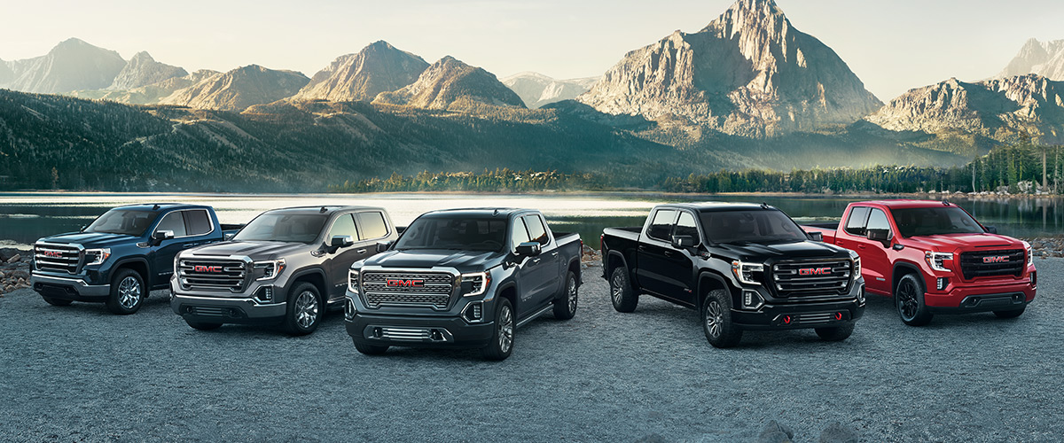 GMC Truck lineup with mountain scenery in the background