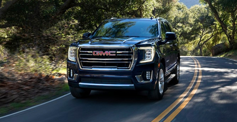 Front shot of the 2021 GMC Yukon driving along a road