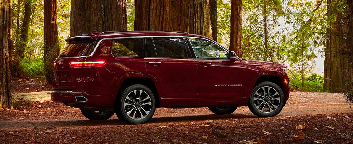 2021 Jeep Grand Cherokee L driving through wooded area