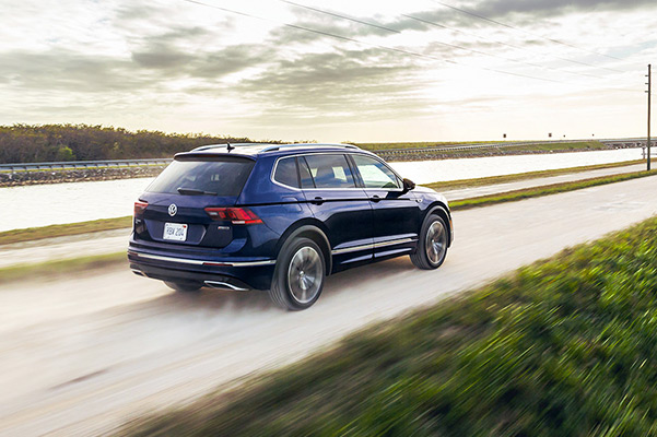 A Tiguan in Atlantic Blue Metallic seen from behind driving along a canal with trees in the background.