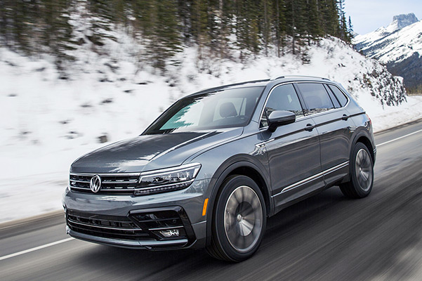 A Tiguan in Platinum Gray Metallic driving on a road as seen from the front with snowy mountains in the background.