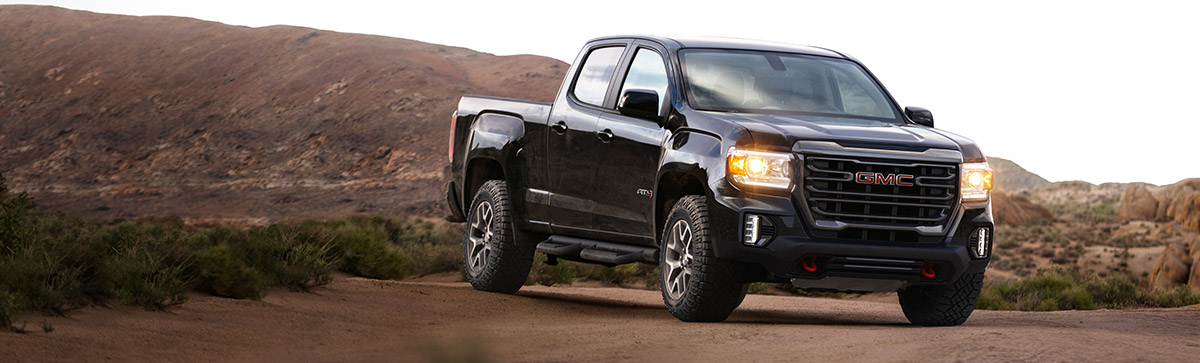 2022 GMC Canyon AT4 Crew Cab Long Box in Onyx Black with (R1U) 17 inch Dark Argent Metallic Cast Aluminum Wheels; Shown with Accessory Assist Steps and Skid Plate; 3/4 Passengers side Front; Desert background
