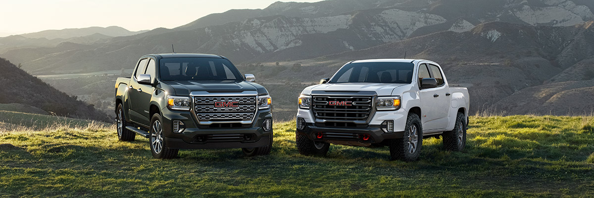 2022 GMC Canyon 2-Truck Pack, Family Shot; Featuring (L to R) Canyon Denali Crew Cab Short Box in Hunter Metallic with (RQ9) 20 inch Diamond Cut Machined Aluminum Wheels and Canyon AT4 Crew Cab Short Box in Summit White with (R1U) 17 inch Dark Argent Metallic Cast Aluminum Wheels; Mountains in background.