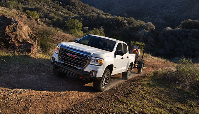 2022 GMC Canyon AT4 Crew Cab Short Box in Summit White with (R1U) 17 inch Dark Argent Metallic Cast Aluminum Wheels; Shown with Front Accessory Skid Plate; 3/4 Drivers side Front; Road shot/motion; Mountains in background
