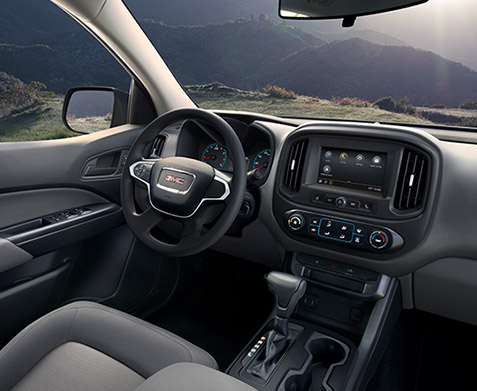 2022 GMC Canyon Elevation Standard Interior Cockpit in Jet Black/Dark Ash; Drivers Seat; View from Passengers side rear; Showing Center Console, Cup Holders, Shifter, and Available 7 inch Diagonal Color Touch-Screen Audio System with Navigation and GMC Infotainment; Mountains in background