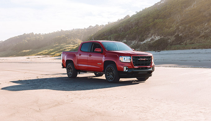 2022 GMC Canyon Elevation Crew Cab Short Box in Cayenne Red Tintcoat with (RCW) 18 inch Black Painted Aluminum Wheels; 3/4 Passengers side Front; Parked on beach