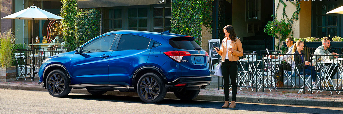 Blue 2022 Honda HR-V park out front of a restaurant with woman answering phone with coffee in hand.