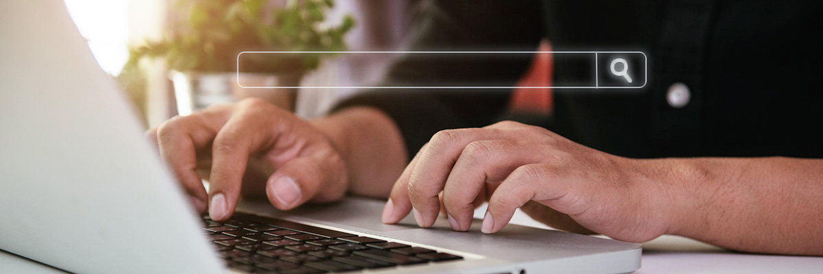 Close up of hands on a laptop keyboard with a search bar overlayed on the image