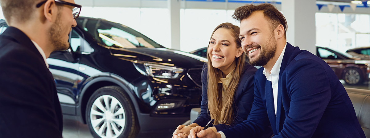 customers speaking with salesperson at a car dealership