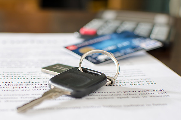 Car keys sitting on a pile of paperwork with a credit card and caluculator blurred out in the background