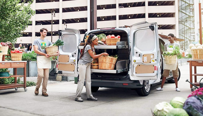 People at a farmers market putting the 2020 Ford Transit Connect Cargo Van to work