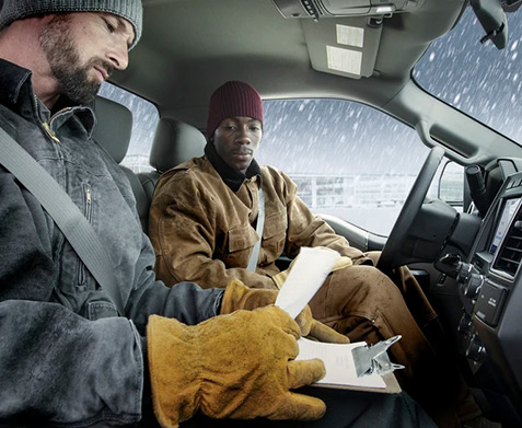 Construction employees doing paperwork in the cab of a Ford Commerical truck