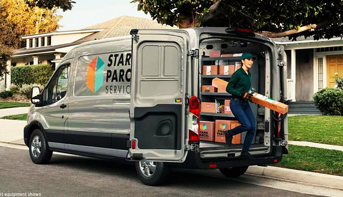 Female employee delivering a package from a Ford transit van