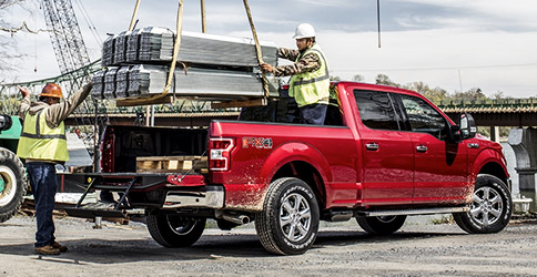 Workers loading heavy cargo into bed of 2020 Ford F-150