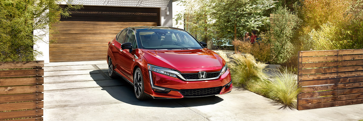 Red 2020 Honda Clarity parked in a modern driveway