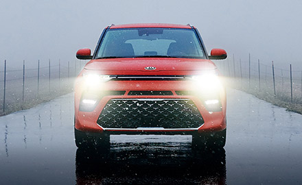 Front view of red Kia Soul on rainy day