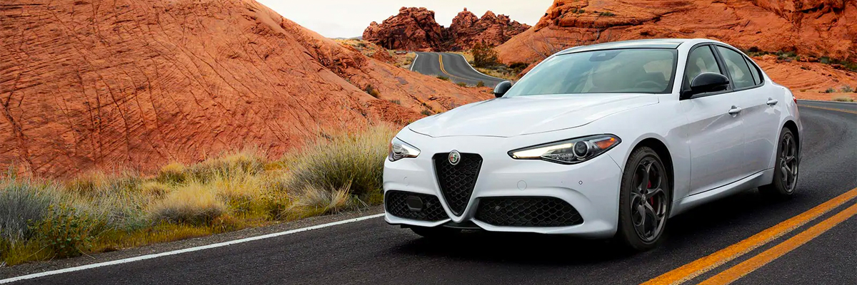 A head-on view of a 2021 Alfa Romeo Giulia Ti Sport Carbon in red, being driven on a winding mountain road.