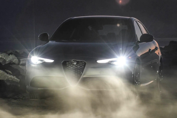 front shot of the 2021 Alfa Romeo Giulia at night with the headlights on