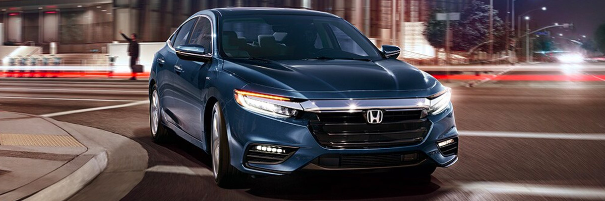 2021 Honda Insight Touring shown in Cosmic Blue Metallic rounding a corner of a city street