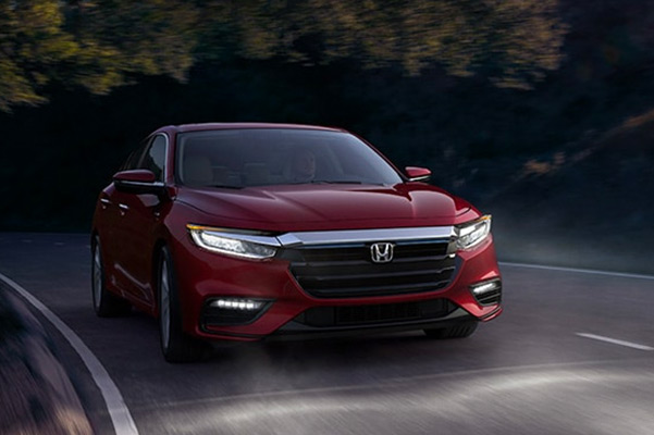 2021 Honda Insight shown in Radient Red Metallic driving down a foggy road