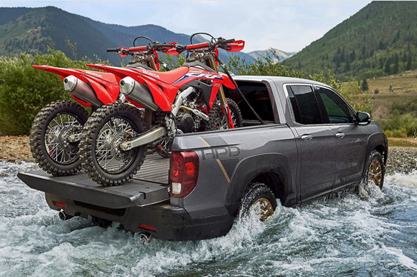 RTL-E shown in Modern Steel Metallic with HPD™ Package. Towing two Honda motorcycles across a small body of water with mountains in the background.