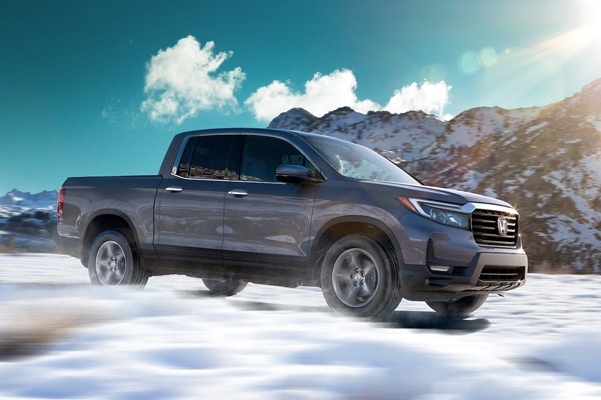 Front driver-side view of the 2021 Honda Ridgeline RTL-E in Modern Steel Metallic driving through snow.