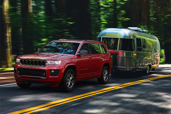 2021 Jeep Grand Cherokee L towing a camper down a scenic road