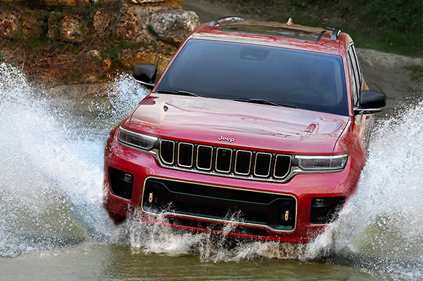 2021 Jeep Grand Cherokee L driving through a flooded road