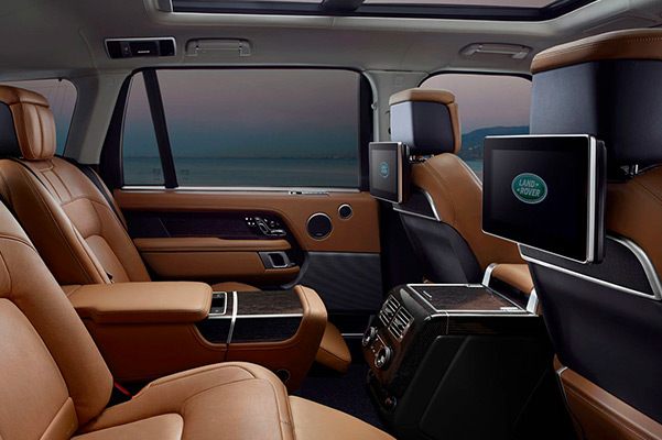 Interior shot of the back seat in a 2021 Range Rover with flatscreens mounted on the back of the font seats