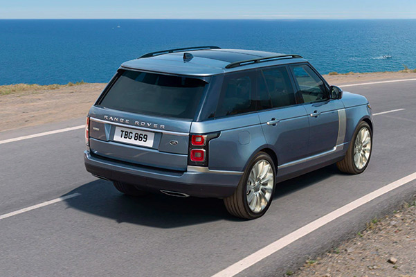 Rear view of a 2021 Range Rover driving down a scenic road