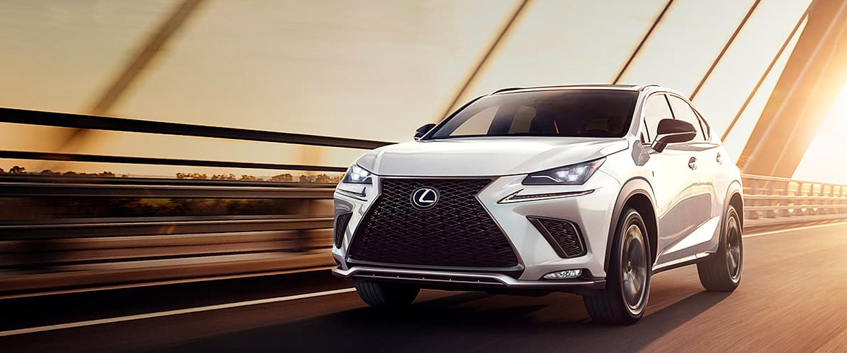 Exterior of the Lexus NX shown in action driving across a bridge at sunset