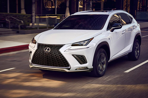 Exterior shot of a 2021 Lexus NX coming to a stop at an intersection