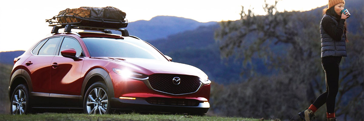 Front view of Mazda CX-30 on grass by mountain side