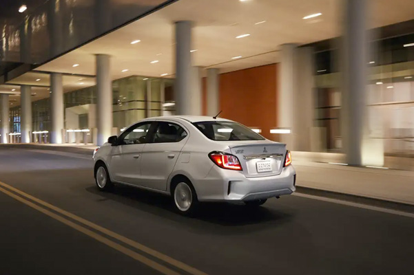 A rear exterior view of a silver 2021 Mitsubishi Mirage G4 parked outside of a modern building with columns.