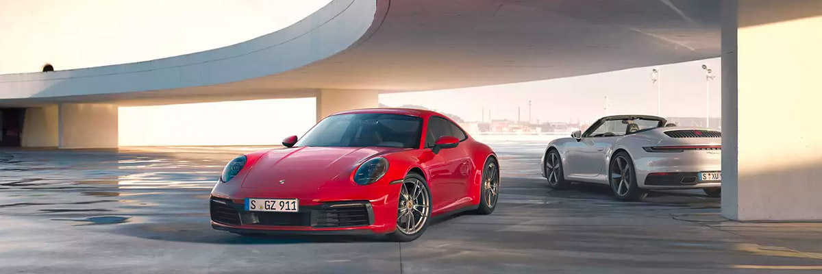 Two 2021 Porsche 911 models parked away from each other underneath an overpass