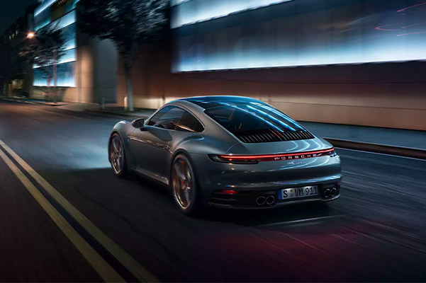 Rear shot of the 2021 Porsche 911 driving down a one lane highway at night