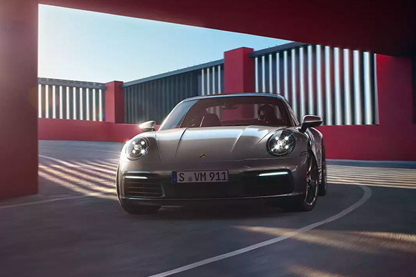 Front view of the 2021 Porsche 911 taking a curve through a tunnel