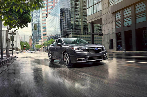 2021 Subaru Legacy driving in a city with wet streets