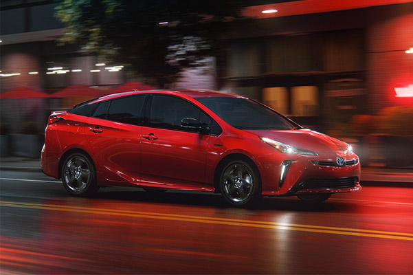 Red Toyota Prius driving on city road at night