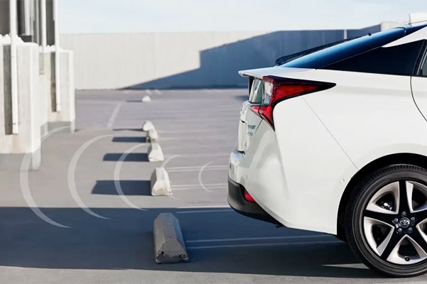 White Prius backing up into parking spot showing Intelligent Clearance Sonar system