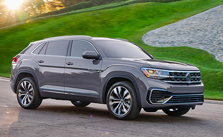 2021 VW Atlas Cross Sport shown driving down a road on a sunny day