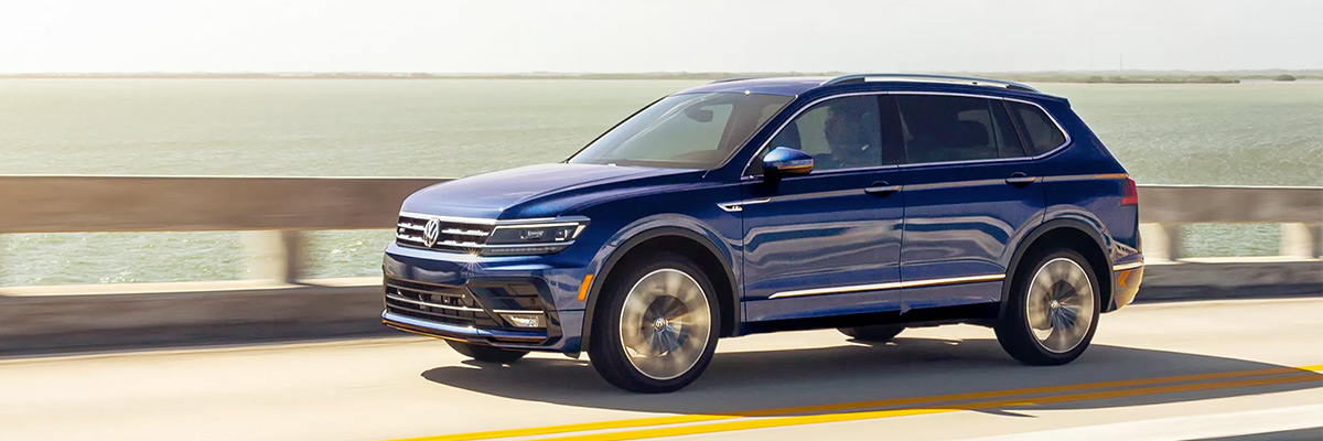 A Tiguan in Atlantic Blue Metallic cruises along the coast.