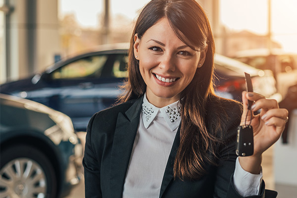 Cheerful young woman showing her new car key at dealership.
