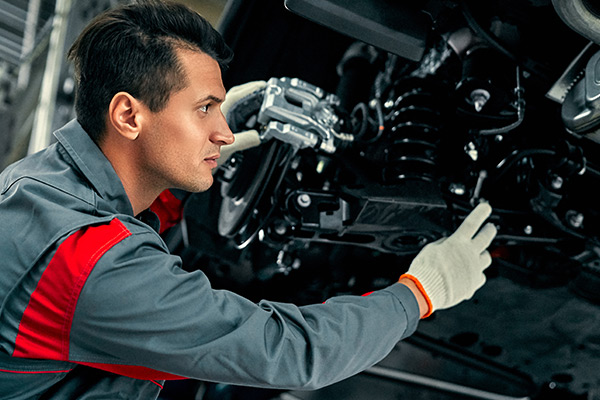 Mechanic in uniform is working in auto service. Car repair and maintenance.