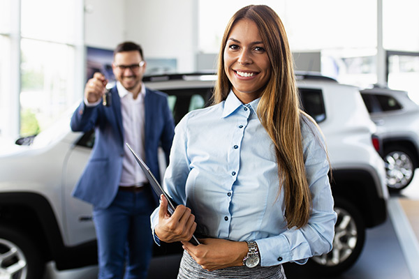Cheerful young woman showing her new car key at DEALER.