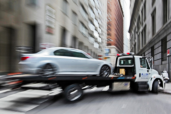 Man delivering vehicle on tow truck