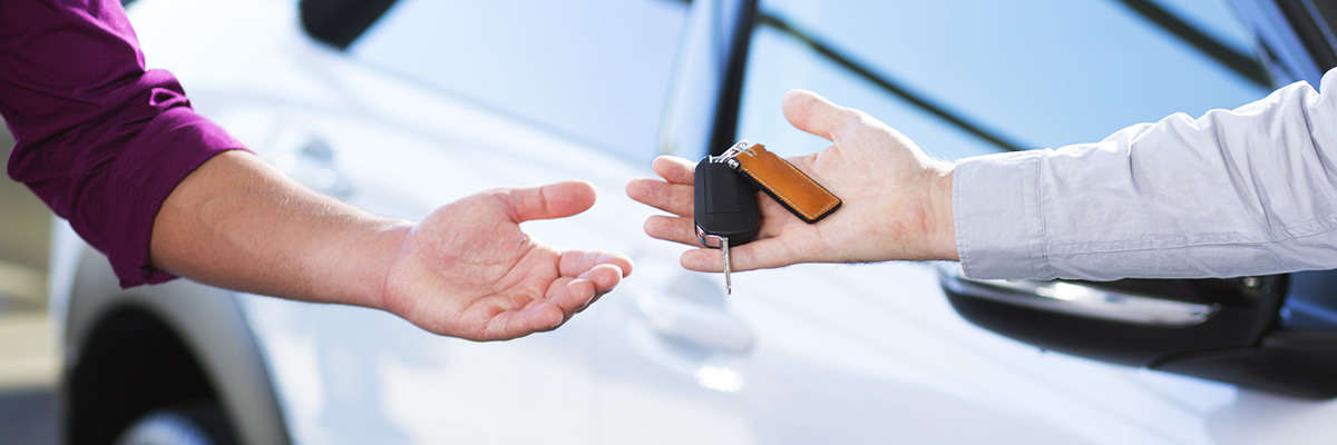 close-up of car seller's hand with keys and buyer's hand after transaction