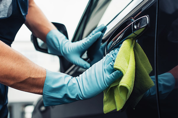 Car cleaner wiping car door with rag