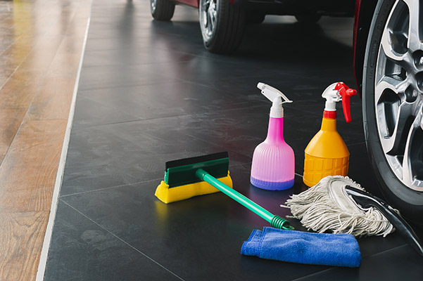 cleaning supplies next to a vehicle inside a dealership